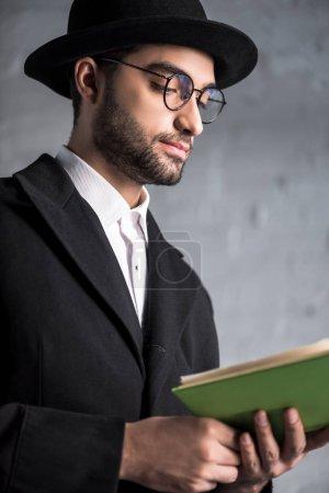 Photo pour Beau et jeune homme juif dans des lunettes livre de lecture - image libre de droit