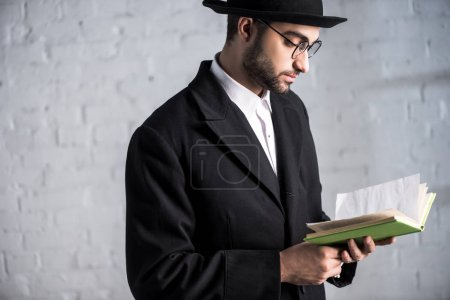 handsome and young jewish man in glasses reading book