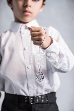 Photo pour Vue recadrée du garçon juif en chemise tenant étoile du collier david - image libre de droit