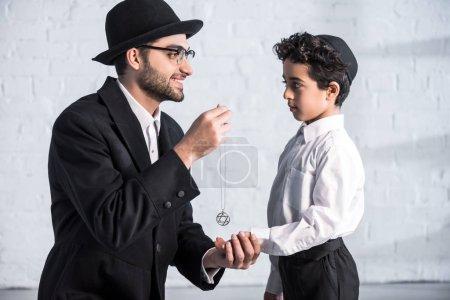 Foto de Vista lateral de sonriente padre judío dando estrella de David collar a hijo - Imagen libre de derechos