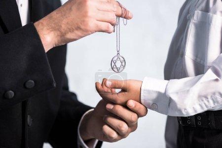 Photo pour Vue recadrée du père juif donnant étoile de collier david fils - image libre de droit