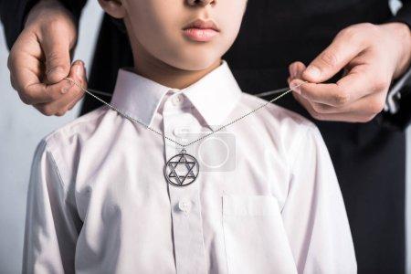 Photo pour Vue recadrée du père juif portant étoile de collier david sur son fils - image libre de droit