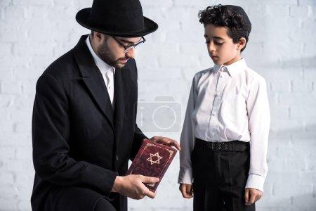 schöner jüdischer Vater mit Tanach und niedlichem Sohn