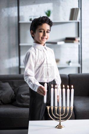 Photo pour Mignon et souriant garçon juif en chemise tenant la bougie - image libre de droit