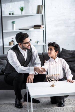 Photo pour Souriant père juif et fils tenant la bougie dans l'appartement - image libre de droit