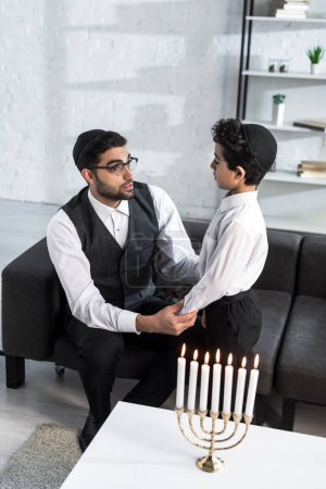 Photo for High angle view of jewish father and cute son talking and holding hands in apartment - Royalty Free Image