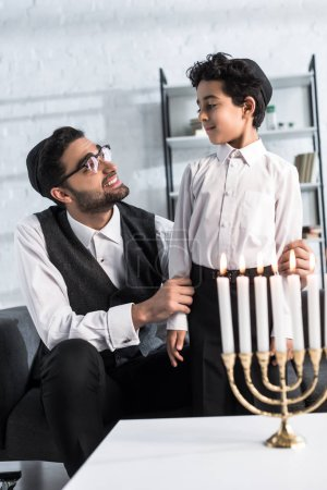 Photo for Smiling jewish father looking at cute son in apartment - Royalty Free Image