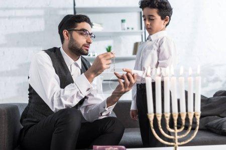 Photo pour Père juif donnant collier au fils mignon dans l'appartement - image libre de droit