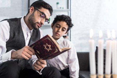 Photo pour Beau père juif et fils lecture tanakh dans l'appartement - image libre de droit