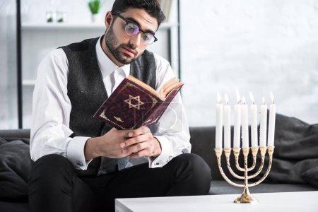 Photo pour Bel homme juif dans des lunettes lecture tanakh dans l'appartement - image libre de droit