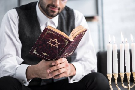 Photo pour Vue recadrée de l'homme juif lisant le tanakh dans l'appartement - image libre de droit