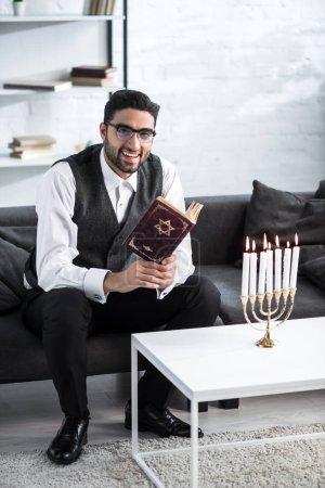 Photo pour Beau et souriant homme juif dans des lunettes tenant tanakh - image libre de droit
