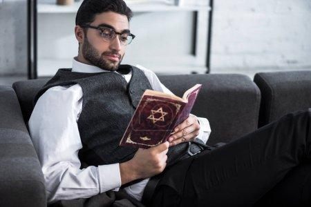 Photo pour Beau et jeune homme juif dans des lunettes lecture tanakh - image libre de droit