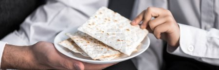 Photo for Panoramic shot of jewish father holding plate and son taking matza in apartment - Royalty Free Image