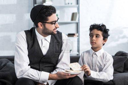 Lächelnder jüdischer Vater mit Teller und Sohn mit Matza in Wohnung