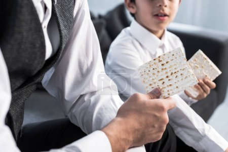 Photo pour Vue recadrée du père et du fils juifs tenant matza dans l'appartement - image libre de droit