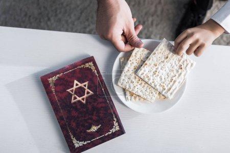 Photo pour Vue recadrée du père et du fils juifs prenant matza dans l'appartement - image libre de droit