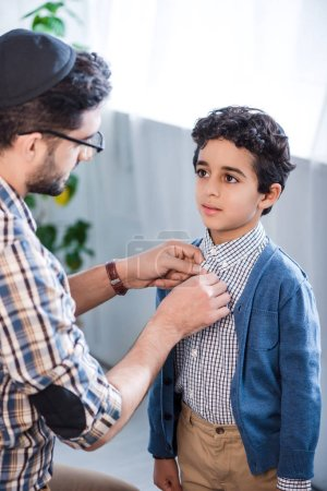 Photo for Jewish father buttoning shirt of cute son in apartment - Royalty Free Image