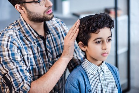 cropped view of jewish father wearing hat on son in apartment