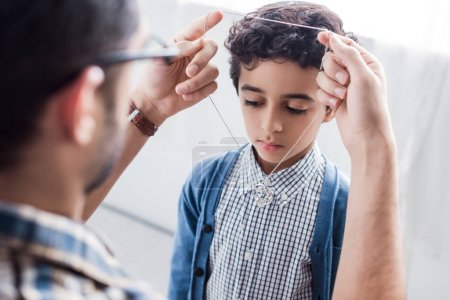 Photo pour Vue recadrée du père juif portant étoile de collier david sur son fils dans l'appartement - image libre de droit