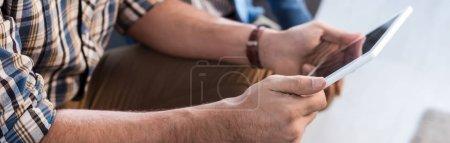 Panoramaaufnahme eines jüdischen Mannes mit digitalem Tablet in Wohnung