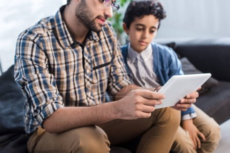 Photo for Cropped view of jewish father and son using digital tablet in apartment - Royalty Free Image