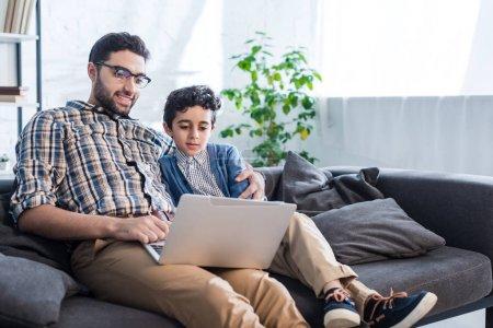 Photo pour Souriant père juif et fils en utilisant un ordinateur portable dans l'appartement - image libre de droit