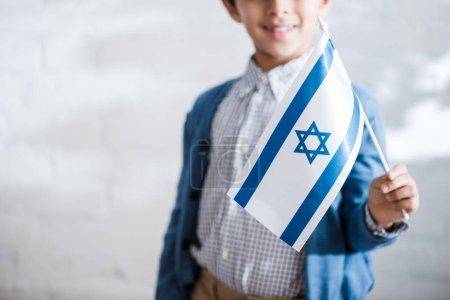 cropped view of smiling jewish boy holding flag of israel