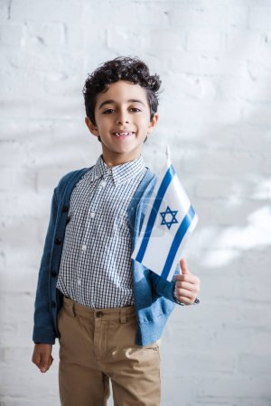 smiling and cute jewish boy holding flag of israel