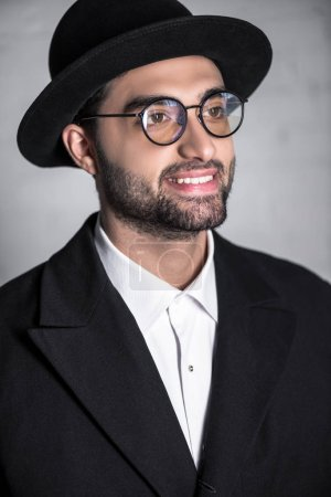 handsome and smiling jewish man in glasses looking away