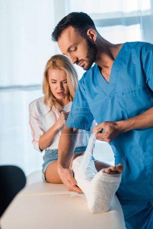 Photo pour Beau orthopédiste mettre bandage sur jambe fracturée de femme effrayée - image libre de droit