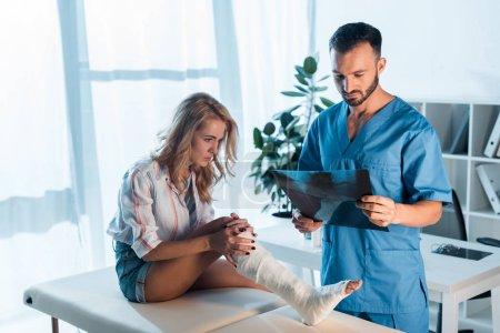 Photo pour Beau orthopédiste barbu tenant rayons X près de femme blessée à la clinique - image libre de droit