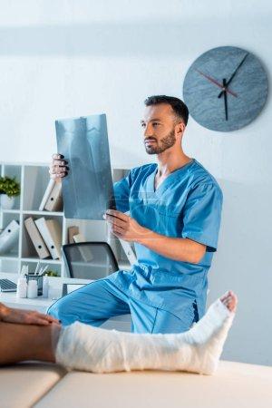 Photo pour Foyer sélectif de l'orthopédiste tenant une radiographie près de la femme blessée - image libre de droit