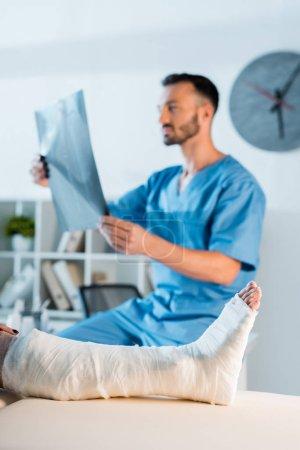 Photo pour Foyer sélectif femme blessée près beau médecin tenant des rayons X - image libre de droit