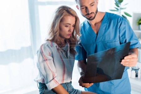 Photo pour Belle orthopédiste et jolie femme regardant les rayons X - image libre de droit