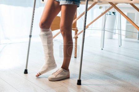 Photo pour Vue recadrée d'une femme fracturée utilisant des béquilles pour se tenir debout en clinique - image libre de droit