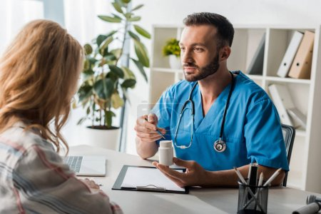 selective focus of handsome doctor holding bottle with pills near woman in clinic