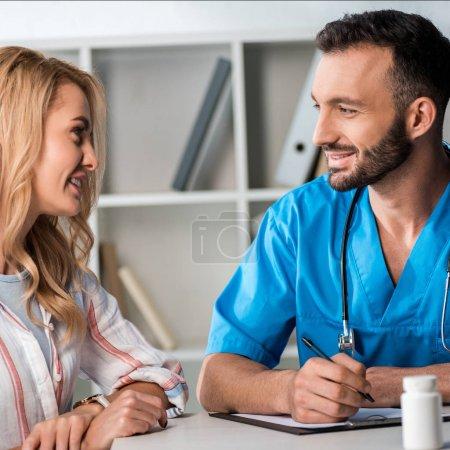 Photo pour Foyer sélectif du médecin barbu heureux tenant le stylo et regardant la femme dans la clinique - image libre de droit