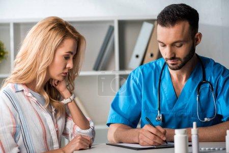 Photo pour Beau docteur barbu écrivant une ordonnance à une femme en clinique - image libre de droit