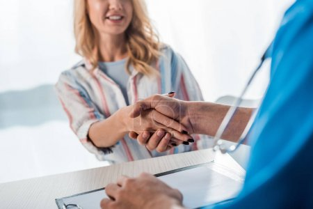 cropped view of happy woman shaking hands with doctor in clinic