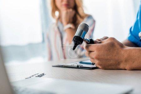 Photo pour Crochet vue d'un médecin tenant un otoscope près d'une femme dans une clinique - image libre de droit