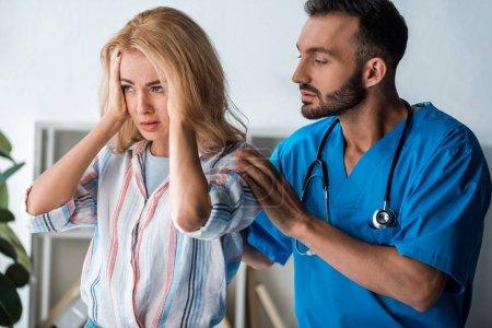 Photo pour Beau médecin touchant femme émotionnelle avec mal de tête - image libre de droit