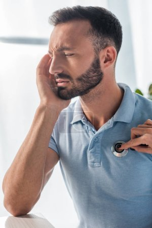 Photo for Cropped view of doctor examining bearded man with headache - Royalty Free Image