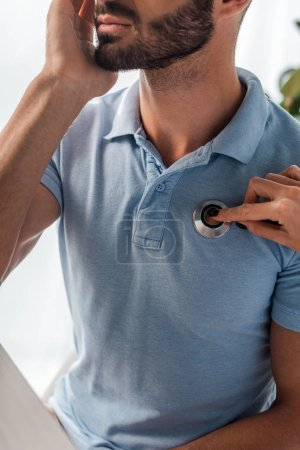 Photo pour Crochet d'un médecin examinant un homme barbu avec un stéthoscope - image libre de droit