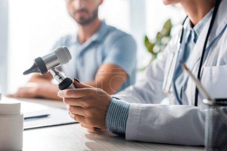 Photo pour Crochet d'un médecin tenant un otoscope près d'un homme dans une clinique - image libre de droit
