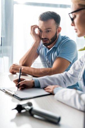 Photo pour Focus sélectif d'un homme barbu en état de choc regardant un médecin établir un diagnostic - image libre de droit