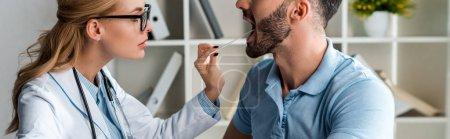 Photo pour Photo panoramique d'un médecin attirant en lunettes examinant un homme avec une spatule médicale - image libre de droit