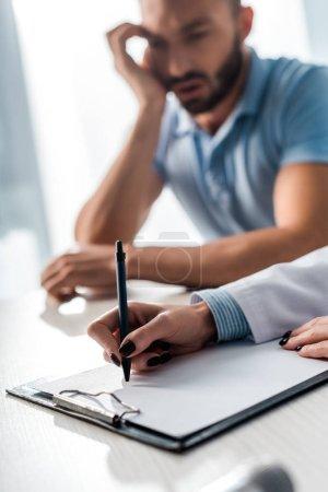 selective focus of doctor writing prescription near sad man