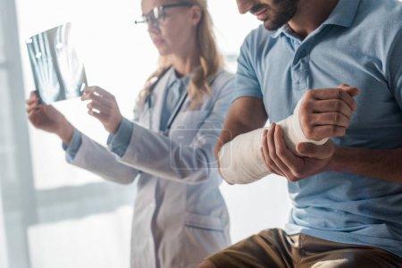 Photo pour Foyer sélectif de l'homme blessé près de médecin attrayant regardant la radiographie - image libre de droit