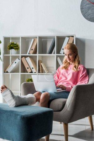 Photo pour Femme blessée travaillant à domicile avec un ordinateur portable - image libre de droit